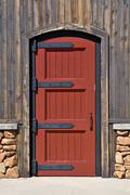 red wood door on wall of house - stock photo