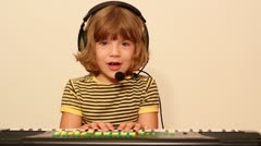 Little girl play music on keyboard Stock Footage