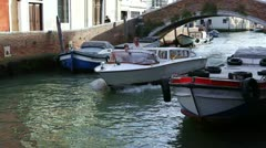 A motor boat passes by on a small canal in Venice Stock Footage