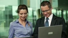 Young business couple with tablet and laptop consulting something Stock Footage