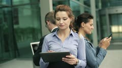 Business people using laptop, tablet and cellphone in the business park - stock footage