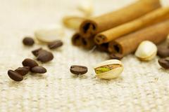 Cinnamon, pistachios and coffee beans on the canvas fabric Stock Photos