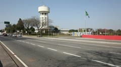 Cars on the avenue and background water tower and flag of brazil Stock Footage