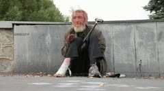 Homeless man sitting on the pavement with a bandaged leg and begging passers Stock Footage