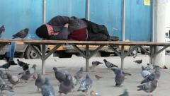 Homeless man sleeping on the bus stop. Stock Footage