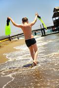 boy goes along seacoast - stock photo
