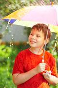 boy under an umbrella during a rain - stock photo