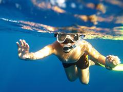 boy floats under water - stock photo