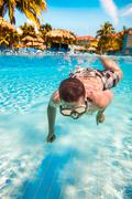 Teenager floats in pool Stock Photos