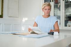 young woman checking bills and doing budget at home - stock photo