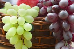red and white grape branch in a basket - stock photo