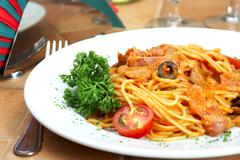 spaghetti with a tomato sauce on a table in cafe - stock photo
