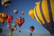 Tourists ride hot air ballons during a mass ascension Stock Photos