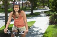 African american woman riding a bike in summer Stock Photos