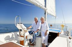 happy senior couple at the wheel of a sail boat - stock photo