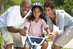 african american family with girl riding bike & happy parents - stock photo