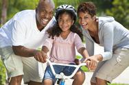 Stock Photo of african american family with girl riding bike & happy parents