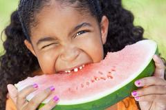 Cute happy african american girl child eating water melon Stock Photos