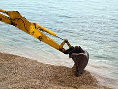 Excavator digging near the sea Stock Photos