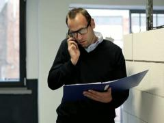 Young businessman with cellphone and documents in the office NTSC Stock Footage