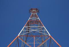 Red triangular power tower in the blue sky - stock photo