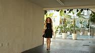 Beautiful fashion female model walking in to focus Stock Footage