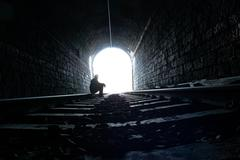 Silhouette at the end of railway tunnel. Stock Photos