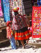 peruvian indian woman looking at colorful textiles - stock photo