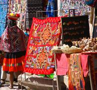 Peruvian indian woman looking at colorful textiles Stock Photos
