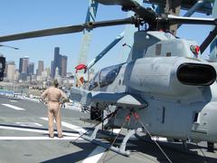 Civilians inspect an ah-1w super cobra helicopter Stock Photos