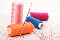 Stock Photo of spool of thread and needle. sew accessories.