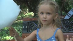 Child Eating Cotton Candy on a Bench in Park, Happy Little Girl, Food, Children - stock footage