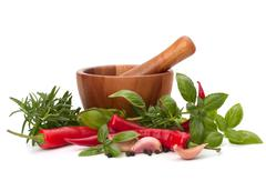 Fresh flavoring herbs and spices in wooden mortar Stock Photos