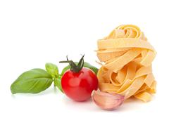 italian pasta fettuccine nest  and cherry tomato - stock photo