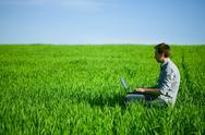 Young man using a laptop outdoors Stock Photos