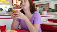 Stock Video Footage of Fast Food - Middle Aged Woman Eating a Hamburger Waist Up