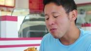 Fast Food - Young Asian Man Eating Hamburger Closeup Stock Footage