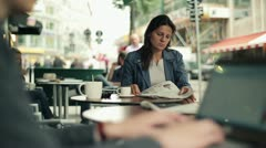 Young businesswoman sitting in restaurant and reading newspaper, outdoors Stock Footage