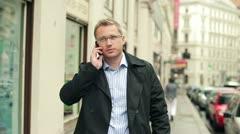 Nuori mies puhuu kännykkään kaupungissa, steadycam ammuttu Arkistovideo