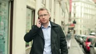 Young man talking on cellphone in the city, steadycam shot Stock Footage