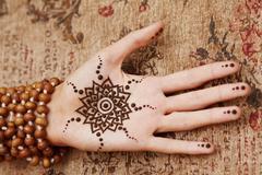 henna art on woman's hand - stock photo