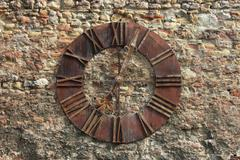 ancient clock face on wall background - stock photo