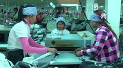 Asian Garment Industry Factory: WS workers feed fabric into rollers - stock footage