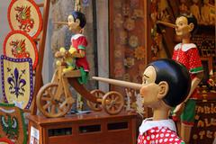 Pinocchio inviting tourists in souvenirs shop Stock Photos