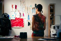 female fashion designer contemplating drawings in studio - stock photo