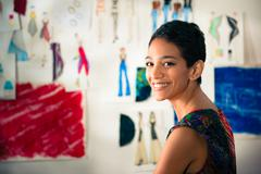 Portrait of happy hispanic young woman working as fashion designer Stock Photos
