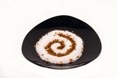 powdered sugar on a black saucer isolated on white - stock photo