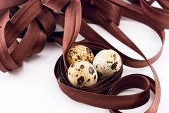 quail eggs and ribbon isolated on white - stock photo