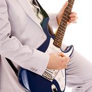 Man in white suit playing guitar Stock Photos