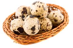 Stock Photo of quail eggs in a basket isolated on white